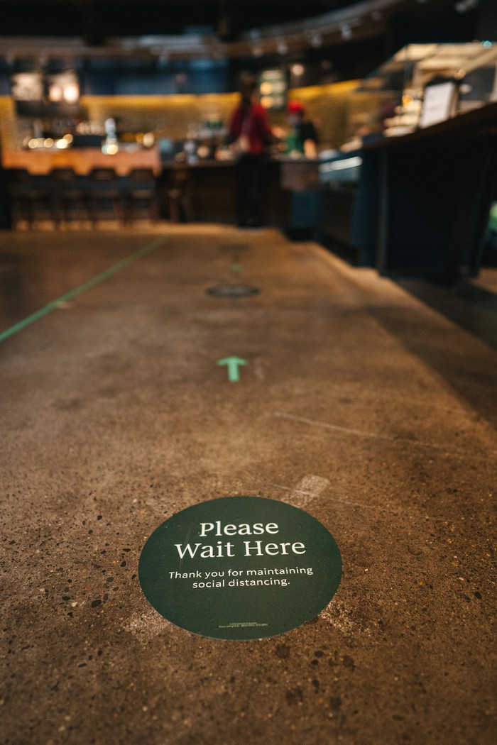 """An entrance to a Starbucks shop is shown, with a sign saying """"Please wait here."""""""