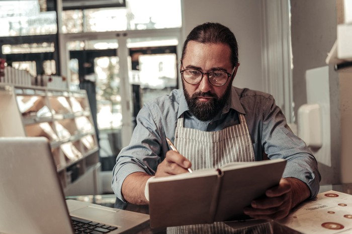 Man in apron with serious expression writing in notebook next to laptop