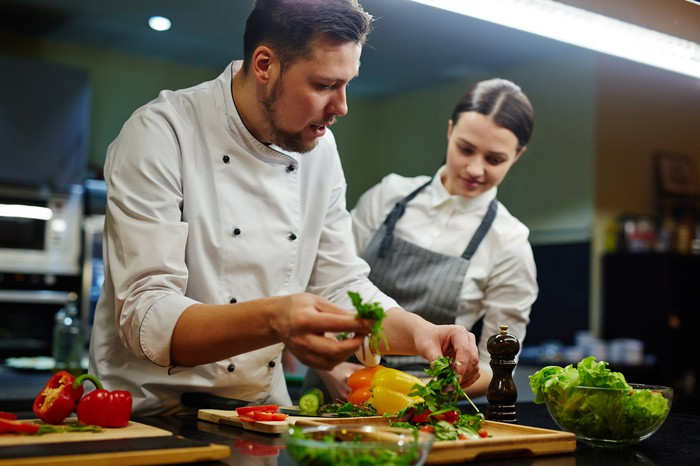 A chef and his assistant preparing food.