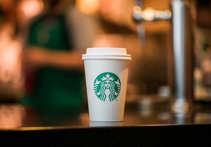 A Starbucks cup on a table against a blurred background.