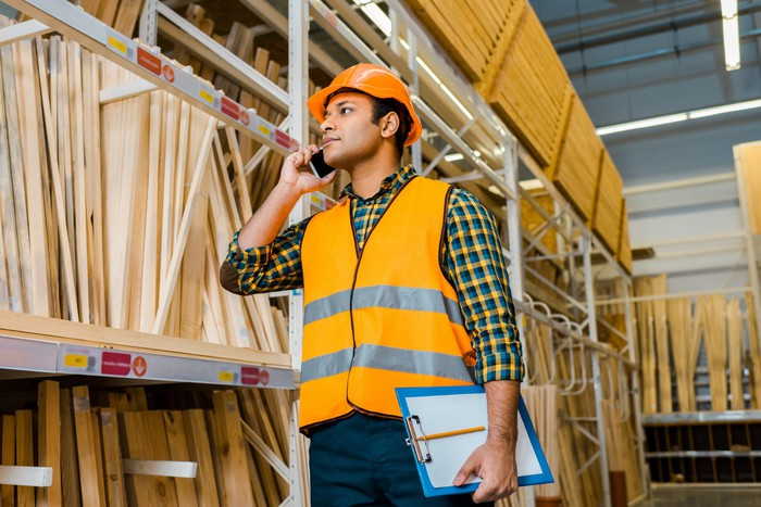 Man wearing hard hat and holding clipboard standing next to shelves stocked with wood