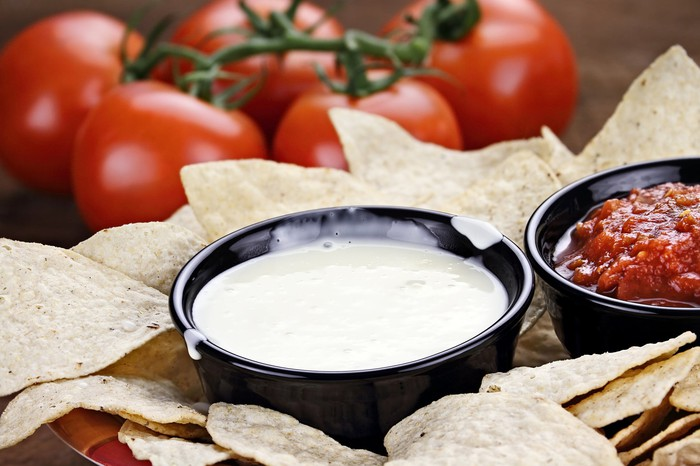 A bowl of generic queso blanco dip with tortilla chips.