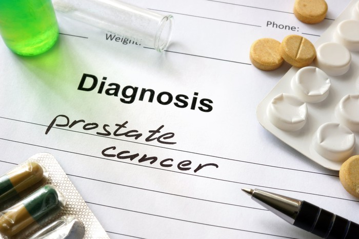 Sheet of paper with Diagnosis prostate cancer with pills and packaging on top