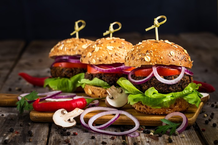 Three veggie burgers, overflowing with lettuce and onions, sit on a wooden surface.