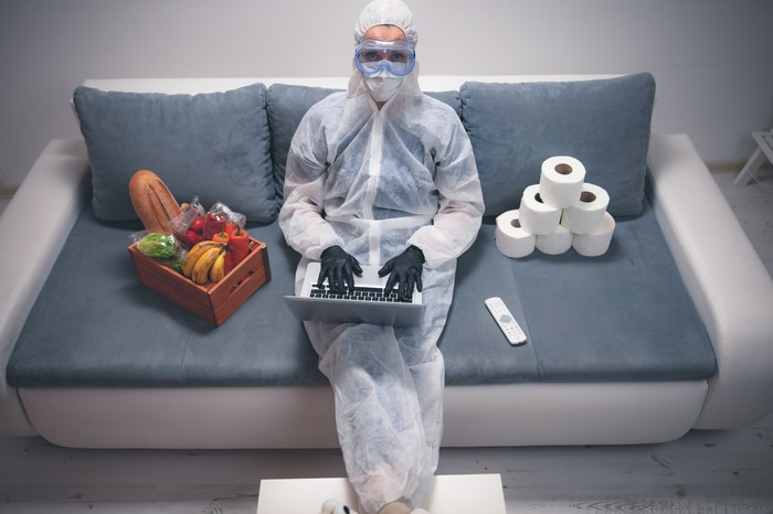 A woman in protective gear sitting on the couch with her laptop with toilet paper and produce beside her.