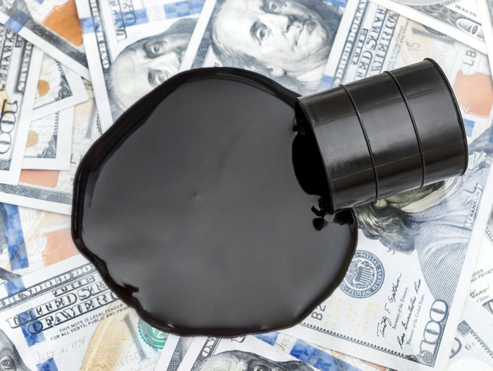 An oil drum spills black liquid onto $100 bills.