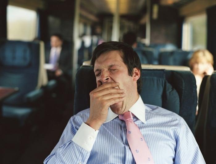 A businessman yawns on a train.