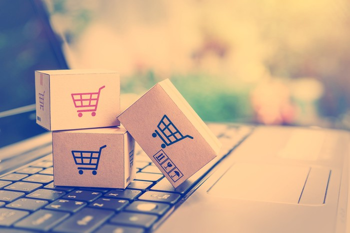 A laptop and miniature packages with shopping-cart icons on them.