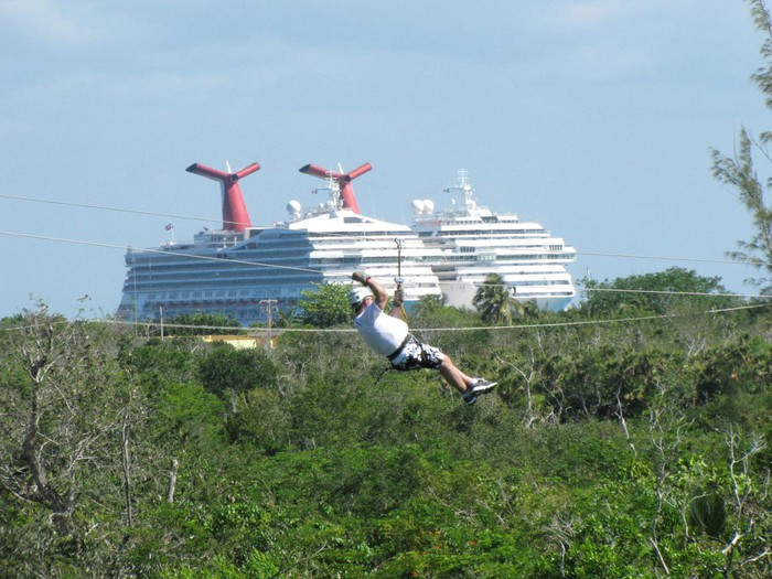 Person on a zipline above a forested area, with a cruise ship in the background.