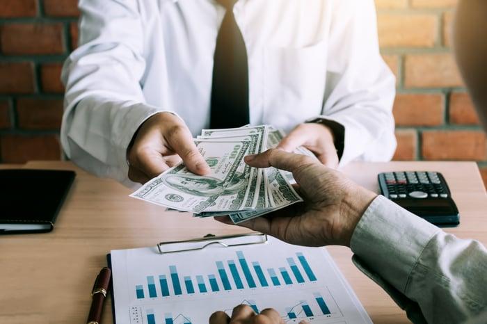 Man receiving a cash payment from a businessman at a desk