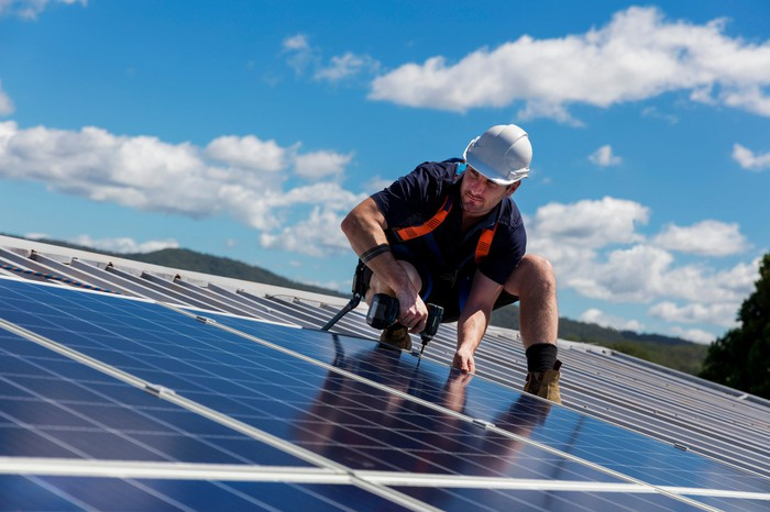 A solar panel installer works with a drill on a roof.