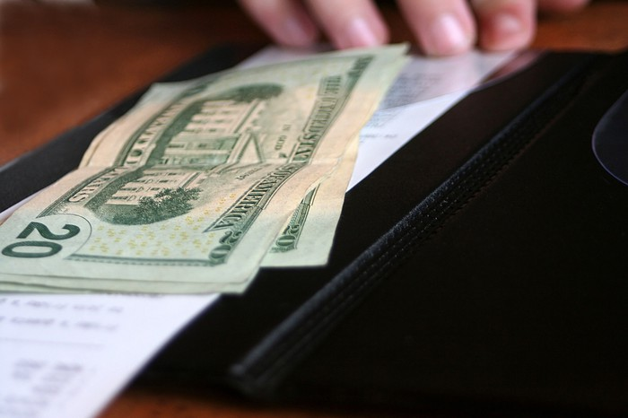 Restaurant billfold with money for a tab.