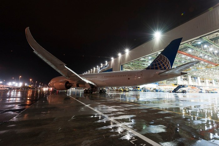 A United 787 leaving the hangar at night.