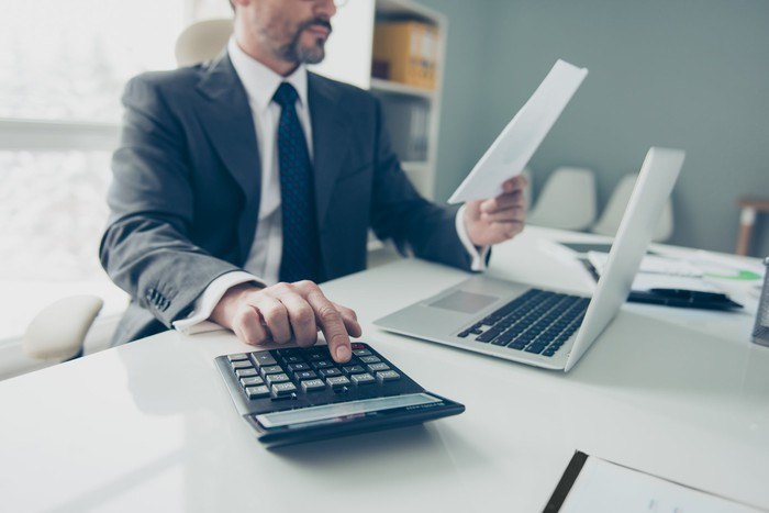 Man in suit reading a financial report and typing numbers into a calculator