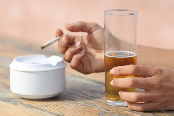 Close-up of person ashing a marijuana cigarette in one hand, and holding a glass of beer in the other.