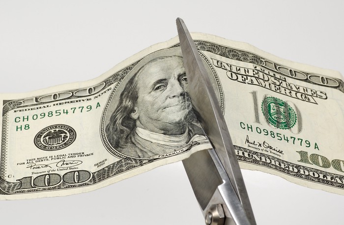 Scissors cutting a one hundred dollar bill in half.
