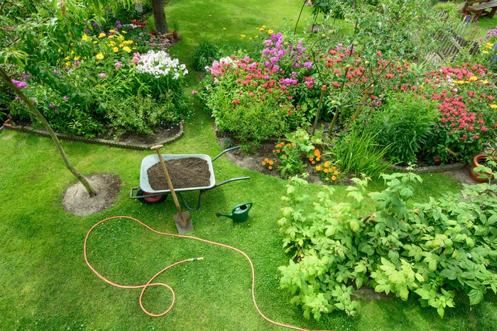 Aerial view of a landscaped yard, with a wheelbarrow filled with soil, a hose, and a watering can.