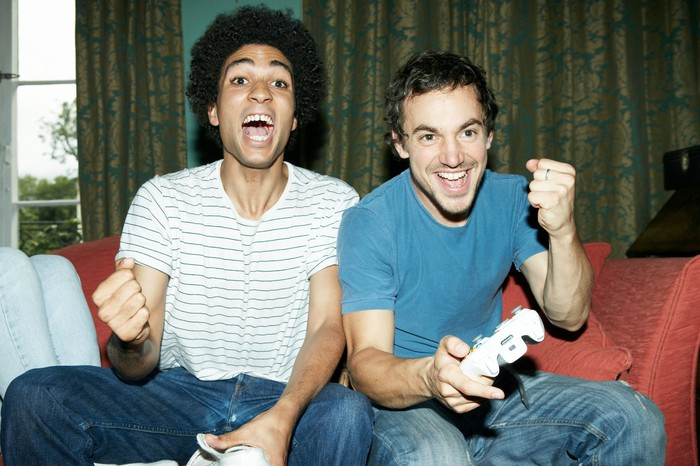 Two young men pump fists in victory at the  TV while playing video games.