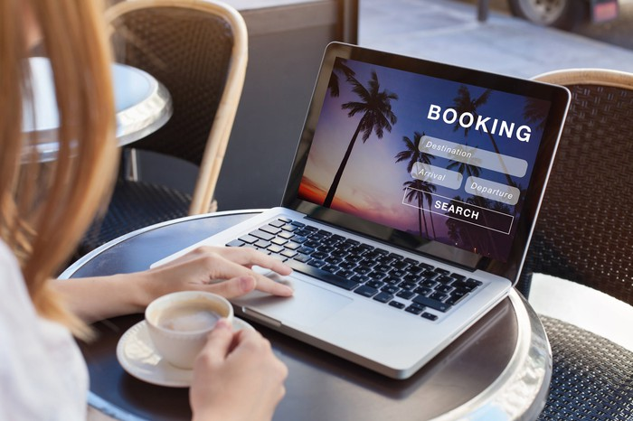 A person sitting at a table with an open laptop showing the word Booking on the screen.