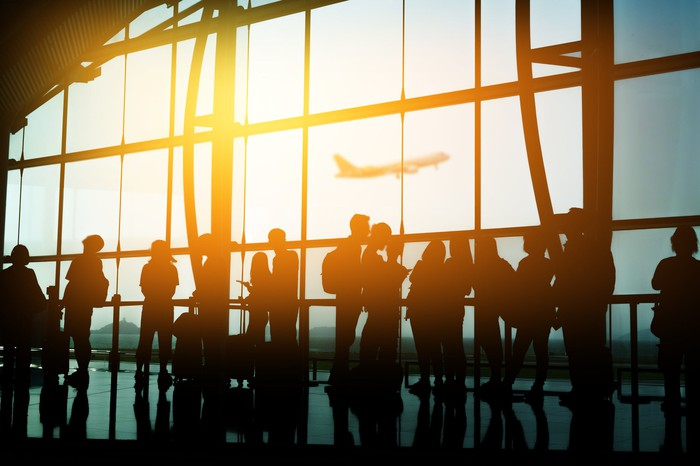 Passengers in silhouette standing in line at an airport terminal.