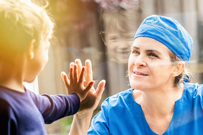 A doctor and a child touch hands through a window