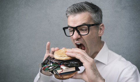 Technology enthusiast eating hamburger made of computer parts_GettyImages-862229634