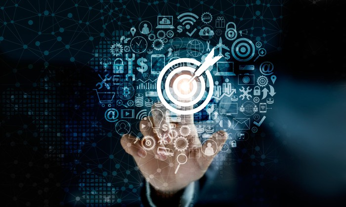 A hand points to a bullseye in the center of a floating cloud of icons representing digital services.
