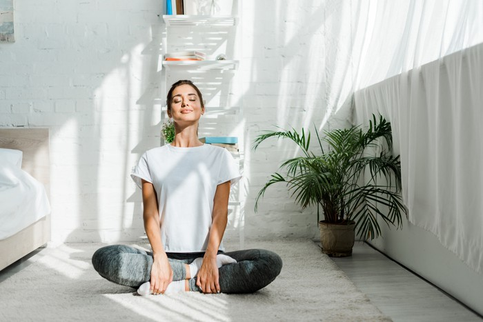 Smiling woman with closed eyes in a yoga pose