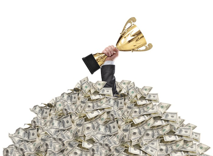 Hand holding trophy sticking through a pile of money