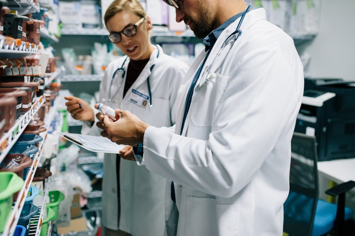 Two pharmacists hold a bottle and discuss