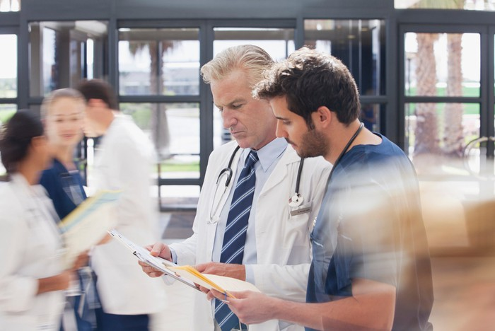 Two medical professionals conferring in a busy hospital lobby.