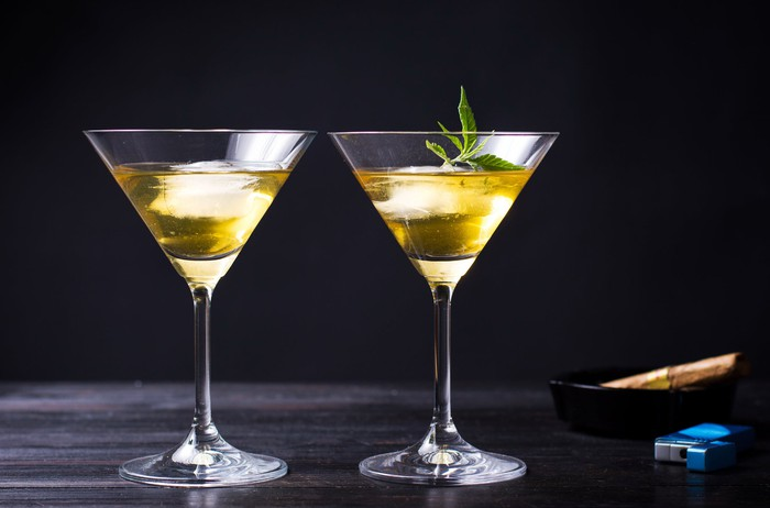 2 martini glasses filled with marijuana-infused drinks next to an ashtray and a lighter.