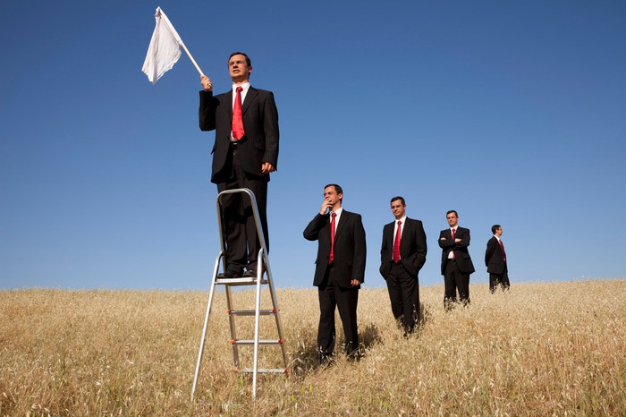 A group of businessmen in a field, getting in line to stand on a stepladder and wave a white flag.