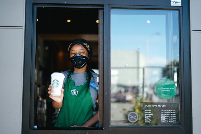 A Starbucks employee wearing a mask serves a coffee through a drive-thru window.