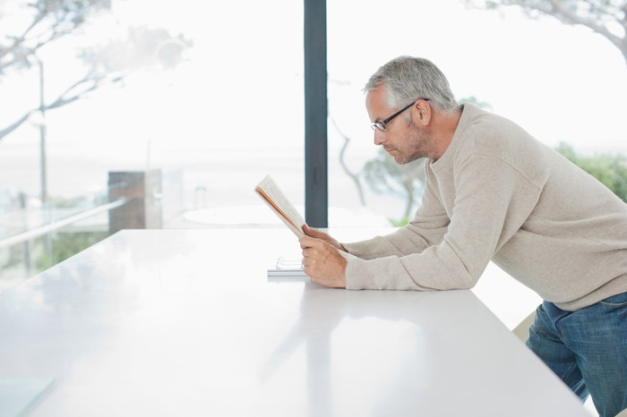 Older man standing at counter while reading