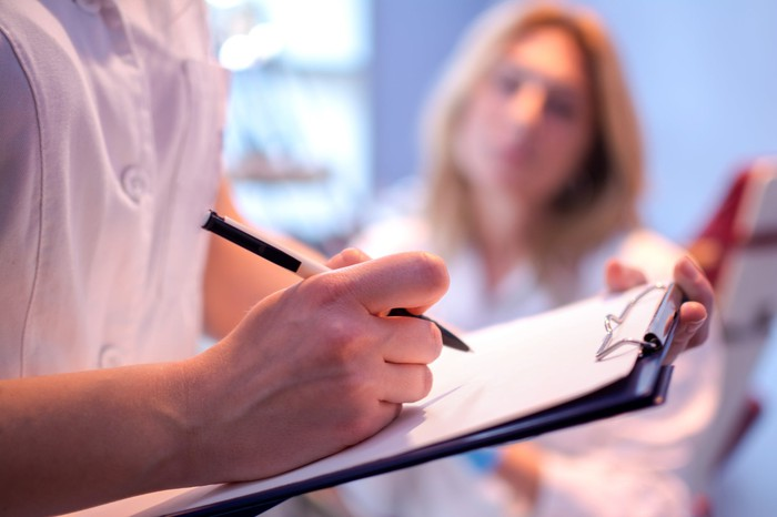 A researcher notes clinical trial data on a clipboard while a patient watches in the background.
