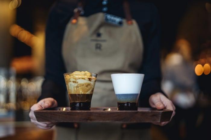 Starbucks worker serving coffee.