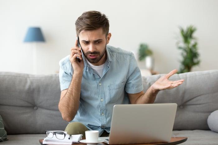 Man at laptop talking on phone