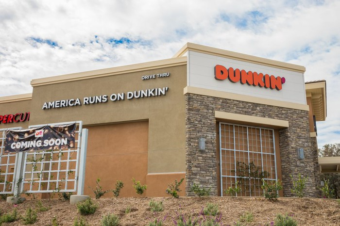 "A Dunkin' outlet with an ""America Runs on Dunkin'"" sign."
