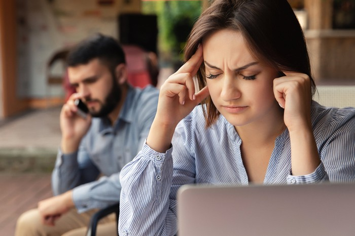 Woman at laptop plugging her ears while man talks on phone behind her