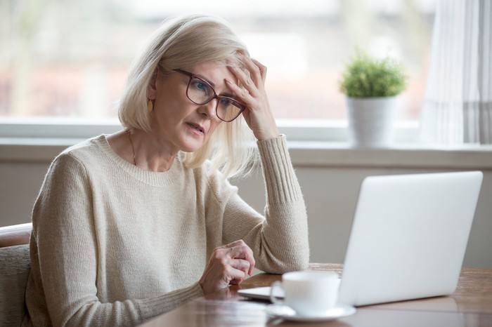 An older woman at her laptop, holding her head and looking worried