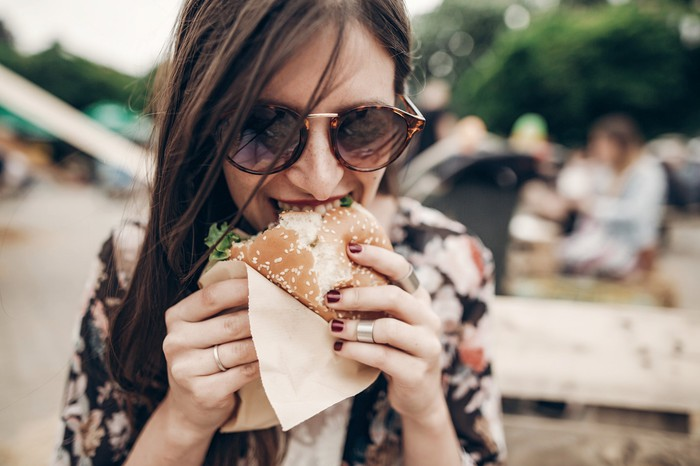 A young woman bites into a burger.