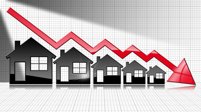 diagram of houses with down arrow indicating drop in housing sales and prices