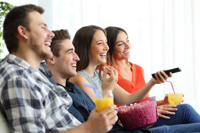 A group of our young friends share drinks and popcorn on a couch, lauching at the unseen TV.