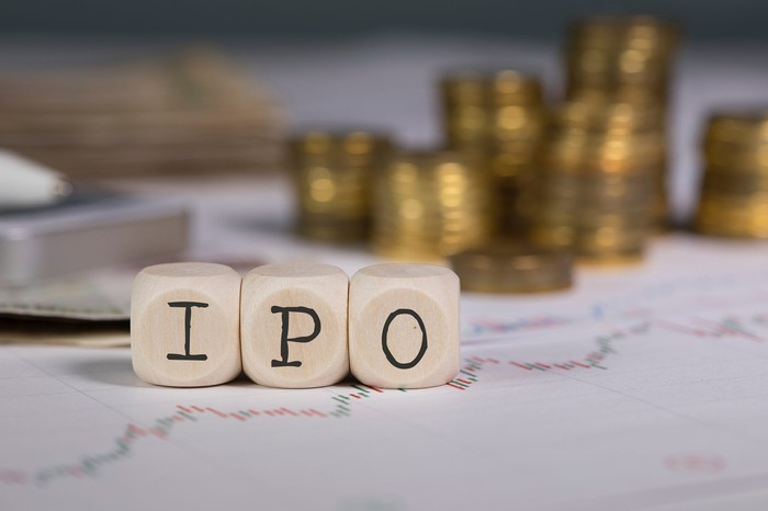 Blocks spelling IPO in front of stacks of coins on top of stock charts