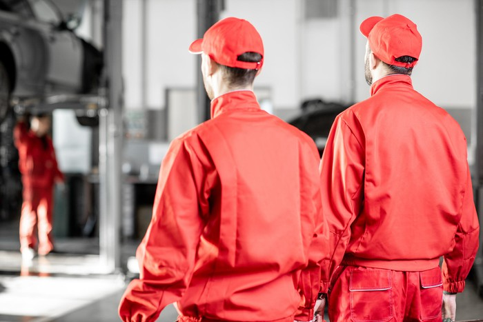 Two men in bright red uniforms in an auto shop.