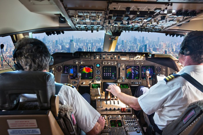 airplane pilots in cockpit with view of city below