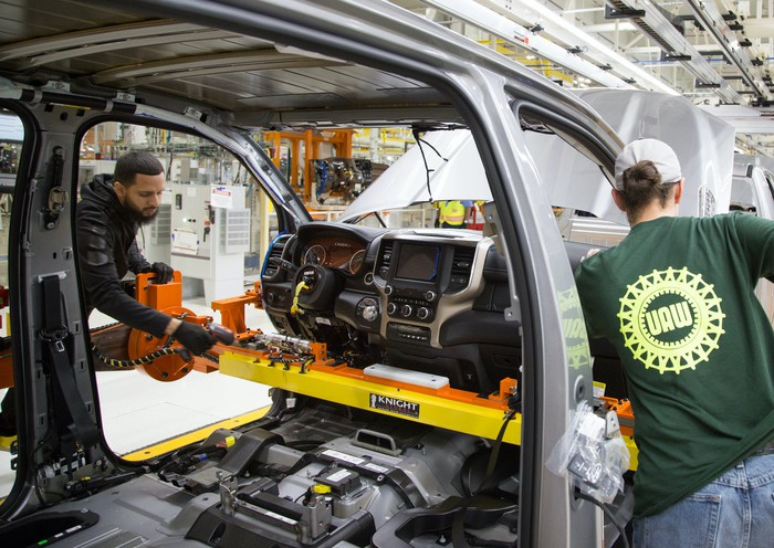 Workers at FCA's Sterling Heights Assembly Plant in Michigan install a dashboard in a Ram 1500 pickup truck.