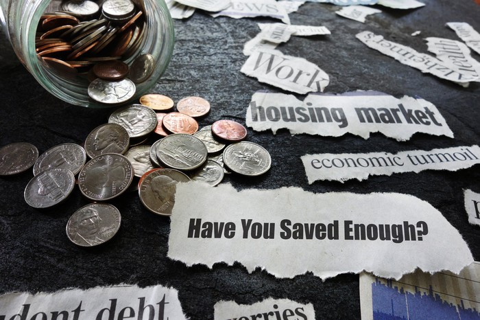 A jar of coins spilled on a table with various notes on it that say Have You Saved Enough? and economic turmoil, among others.