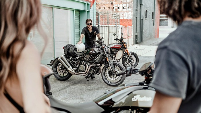 Man standing by motorcycles
